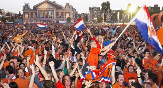 축구 경기를 보며 오렌지색 옷을 입고 열정적으로 응원하는 네덜란드 국민 모습이에요.